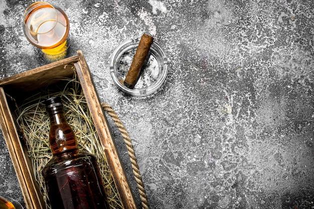 Flasche cognac in einer alten schachtel mit einer zigarre. auf einem rustikalen hintergrund.
