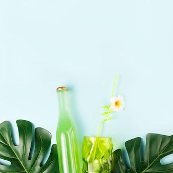 Flasche des getränks nahe glas mit stroh und grünpflanzen