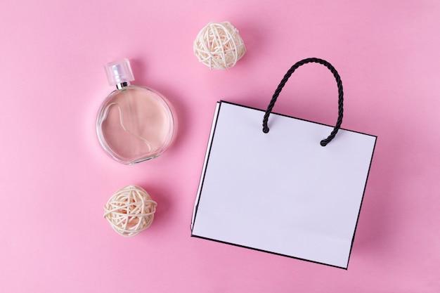 Flasche des lieblingsfrauenparfüms und einer geschenkpapiertüte auf einem rosa hintergrund. draufsicht