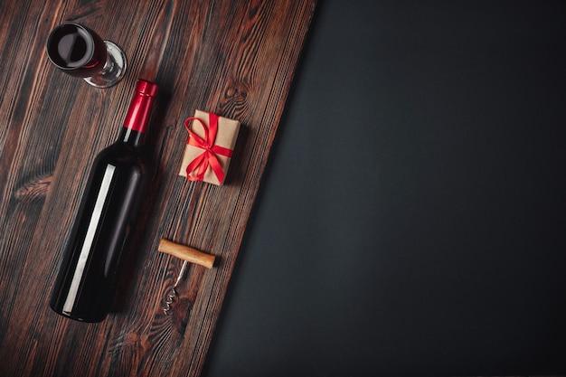 Flasche des weingeschenkboxkorkenziehers und -weinglases auf rostigem