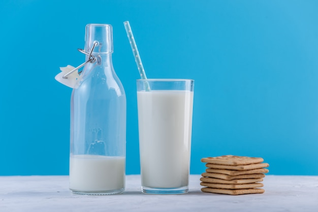 Flasche frische milch mit stroh und plätzchen auf blauem hintergrund. bunter minimalismus. gesunde milchprodukte mit kalzium