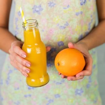 Flasche frischer orangensaft und orange