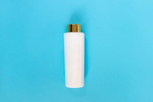 Flasche für flüssigkeit, creme, gel, lotion. kosmetikflasche auf blau. flach liegen