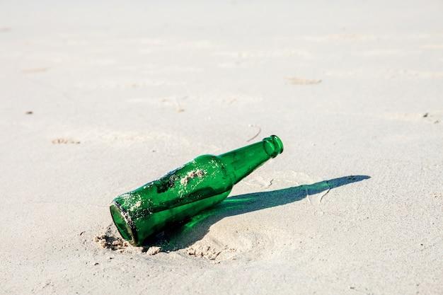 Flasche getränk auf sand.