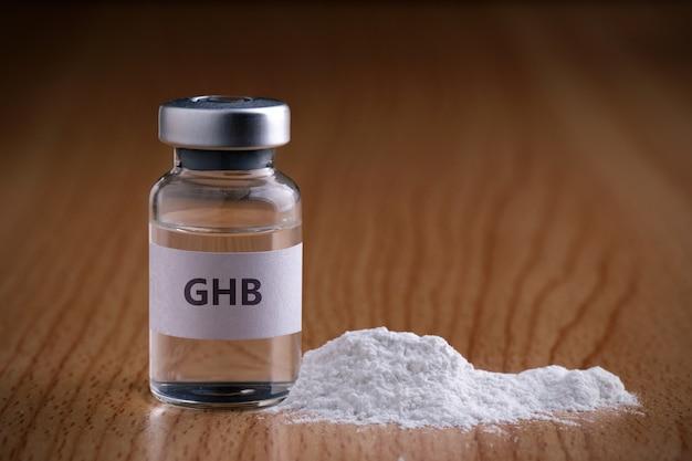 Flasche ghb mit drogenpulver auf holzoberfläche ghb