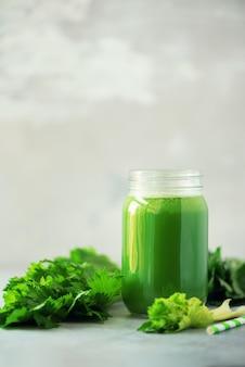 Flasche grüner sellerie smoothie auf grauem konkretem hintergrund