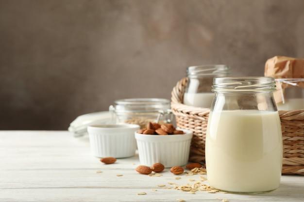 Flasche hafermilch, korb mit einem glas milch verschiedener art auf holz, platz für text