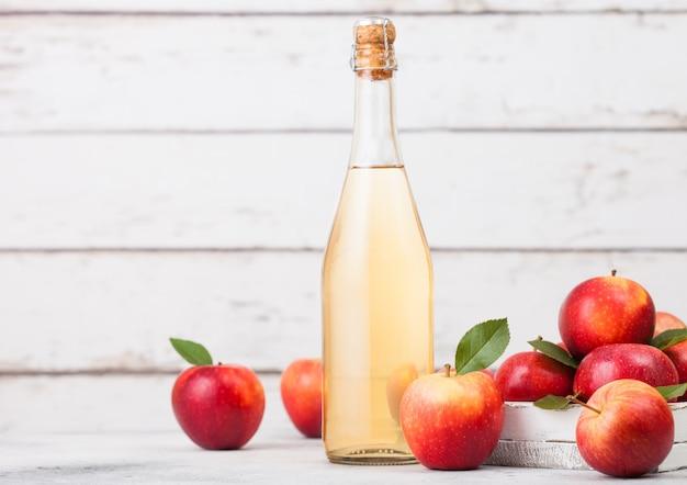 Flasche hausgemachter bio-apfelwein mit frischen äpfeln auf weißem holzhintergrund