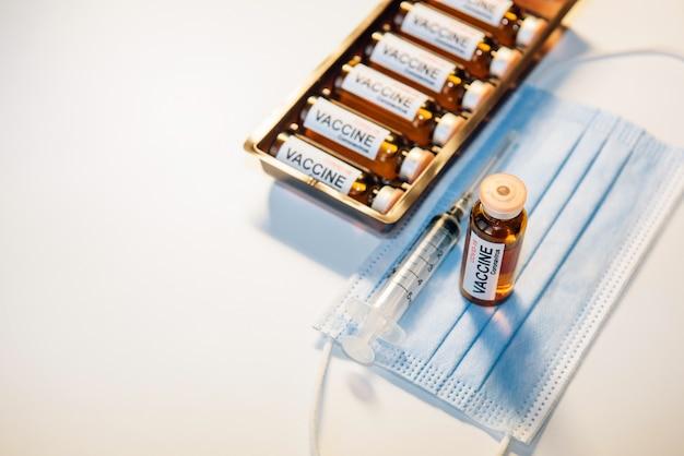 Flasche impfstoff auf blauer medizinischer maske, spritze und ampullenschachtel