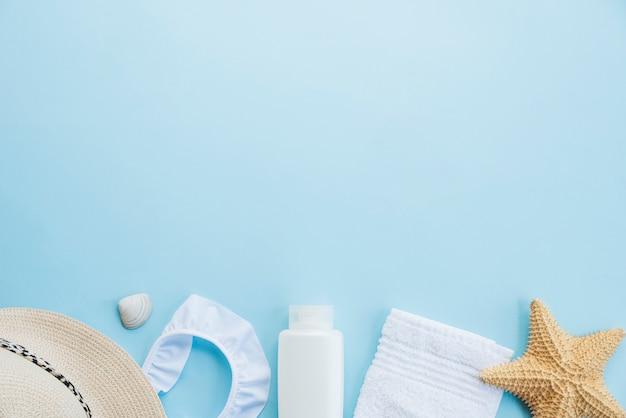 Flasche in der nähe von handtuch mit seestern und hut