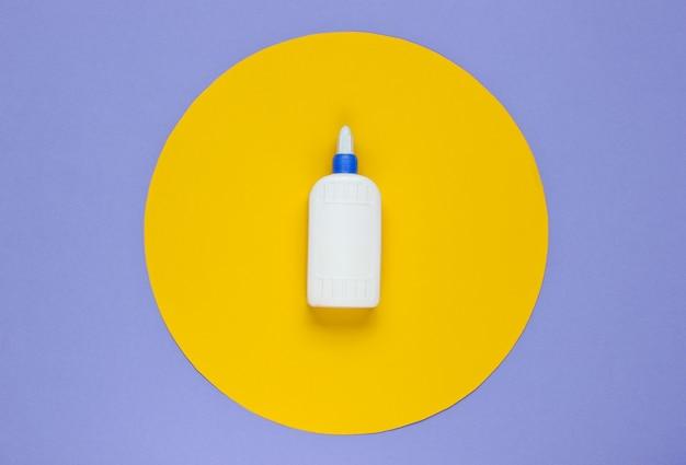 Flasche kleber auf einem lila papier mit gelbem kreis