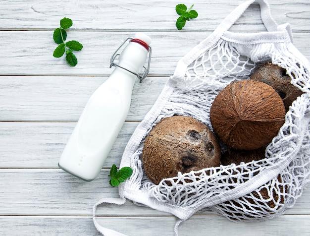 Flasche kokosmilch und kokosnüsse in einem öko-netzbeutel auf einem holztisch
