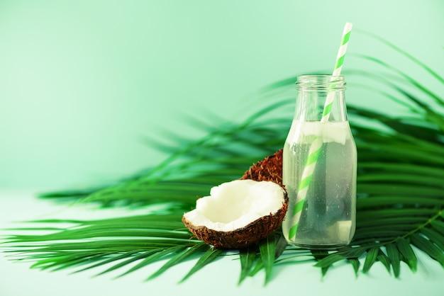Flasche kokoswasser und frische reife früchte. vegetarisches, veganes, entgiftendes getränk. kokosnusssaft mit stroh auf palmblättern