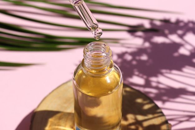 Flasche kosmetisches ätherisches öl mit tropfer auf holzschnitt-serumöl tropft aus tropfer
