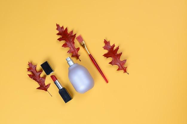 Flasche, lippenstift, pinsel und trockene eichenblätter