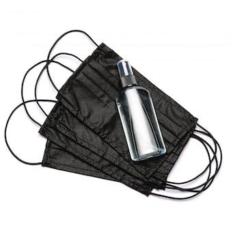 Flasche lotion, desinfektionsmittel oder flüssigseife und medizinische schutzmaske isoliert auf weißer wand mit beschneidungspfad.