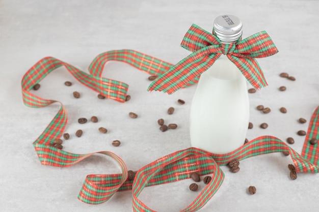 Flasche milch mit band und kaffeebohnen gebunden