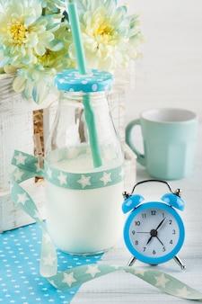 Flasche milch mit stroh und blauem wecker