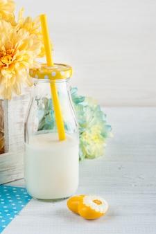 Flasche milch mit stroh und gelbem herzen