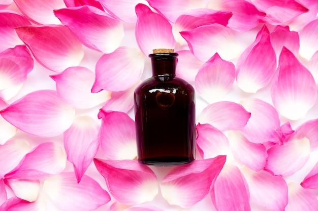 Flasche mit ätherischen ölen auf rosa lotusblütenhintergrund.