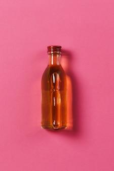 Flasche mit alkohol auf rosa rosenhintergrund