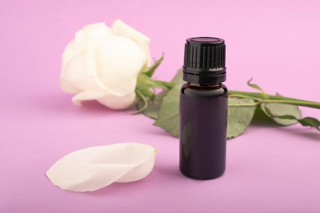 Flasche mit aromatischem öl in den blütenblättern und knospen der weißen rosen