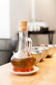 Flasche mit aromatischem pflanzenöl. raffiniertes öl wird mit pfeffer und anderen gewürzen versetzt.