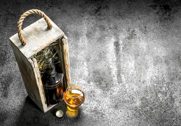 Flasche mit cognac und einem glas.