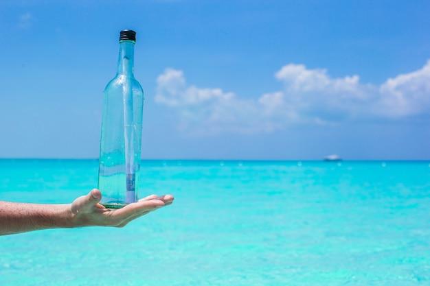Flasche mit einer mitteilung im blauen himmel des handhintergrundes