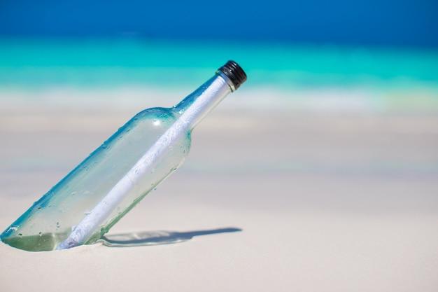 Flasche mit einer nachricht im weißen sand begraben
