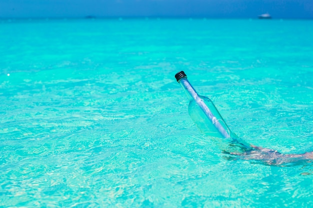 Flasche mit einer nachricht in der hand im meer