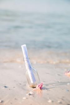 Flasche mit einer nachricht oder einem brief am strand. sos. kopieren sie platz. hilfe.