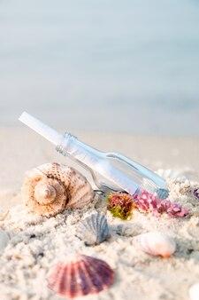 Flasche mit einer nachricht oder einen brief am strand in der nähe von muschel. sos. copyspace.