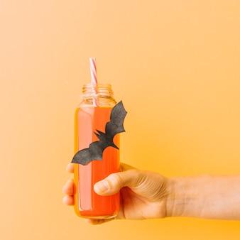 Flasche mit kürbisgetränk und geklebtem schwarzem schläger