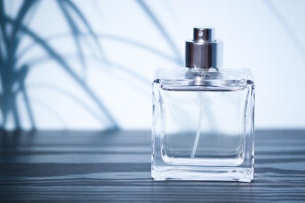 Flasche mit mannparfums mit schatten von exotischen pflanzen.