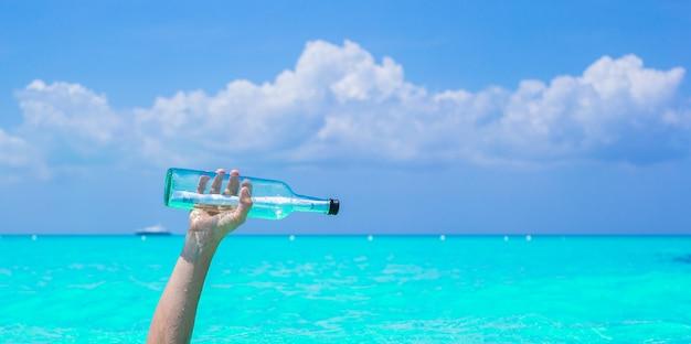 Flasche mit nachricht an der hand
