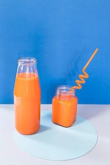 Flasche mit orangefarbenem smoothie auf dem tisch