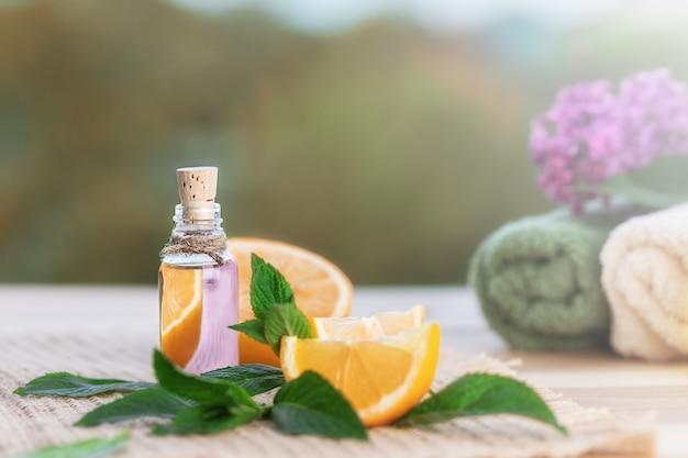 Flasche mit orangenöl, orange und frischen grünen minzblättern auf holztisch. handtücher für spa und flieder im unscharfen natürlichen hintergrund. selektiver fokus.