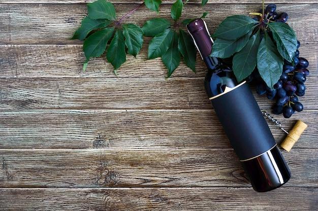 Flasche mit rotem weinkorkenzieher blaue traubenblätter auf einem holztisch wooden