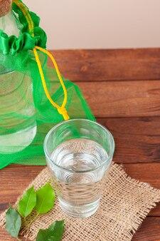 Flasche mit sauberem wasser und den grünen blättern schließen oben