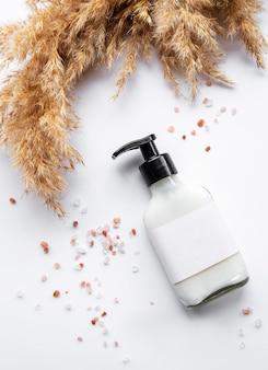 Flasche mit spenderkappe und sauberem etikett, umgeben von braunem pampasgras, auf weißem hintergrund. verpackungskonzept für naturkosmetik, shampoos, cremes. schönheitsindustrie.