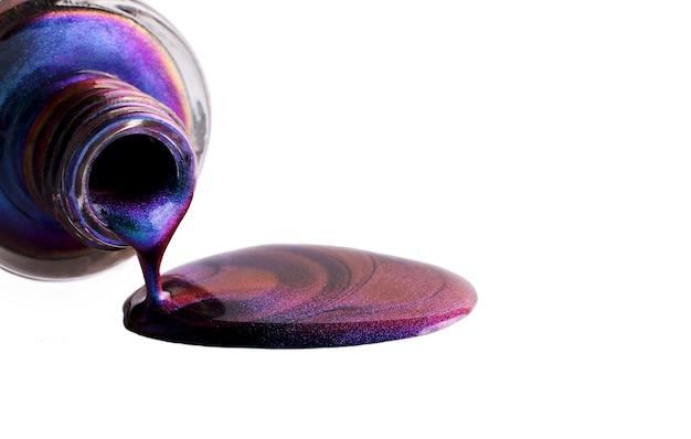 Flasche mit verschüttetem nagellack. bild isoliert auf weiss. schöne schillernde flecken. abstrakter hintergrund.