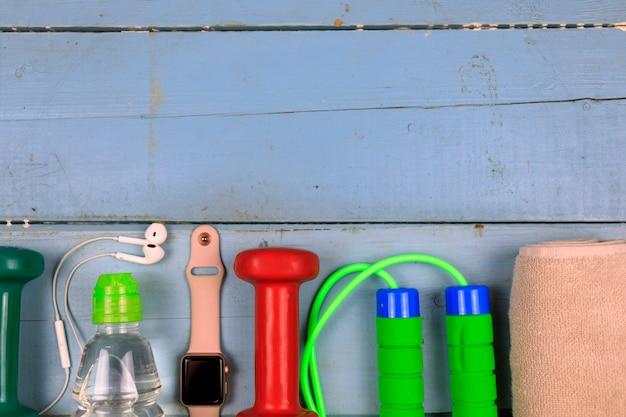 Flasche mit wasser, smartwatch, kopfhörern und springseil.