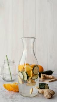 Flasche mit wasser, zitrusfrüchten und gurken