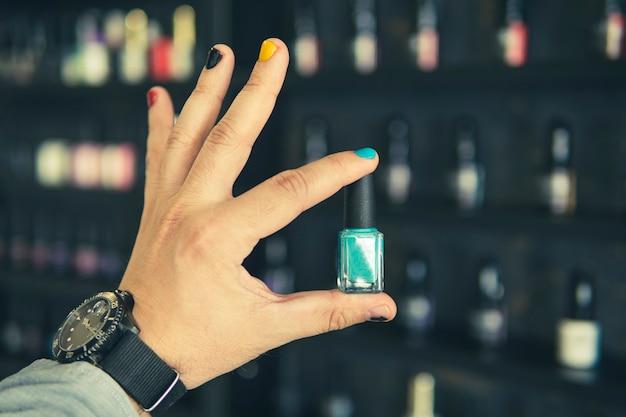 Flasche nagellack in der hand eines mannes mit lackierten nägeln ein mann mit lackierten nägeln. design von männlichen nägeln. männer maniküre.