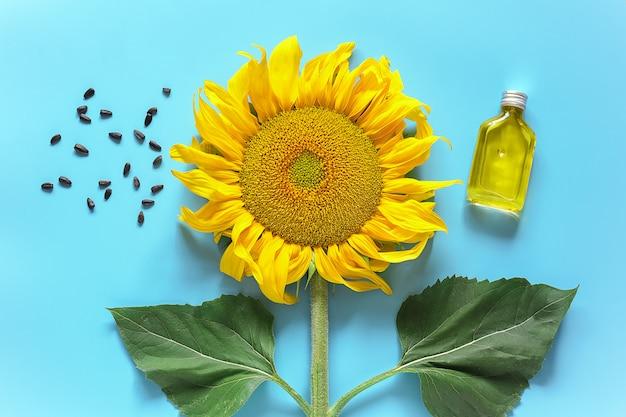 Flasche natürliches sonnenblumenöl, samen und frische gelbe sonnenblume