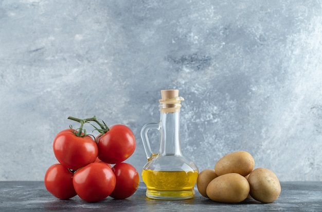 Flasche olivenöl, kartoffeln und tomaten auf marmorhintergrund