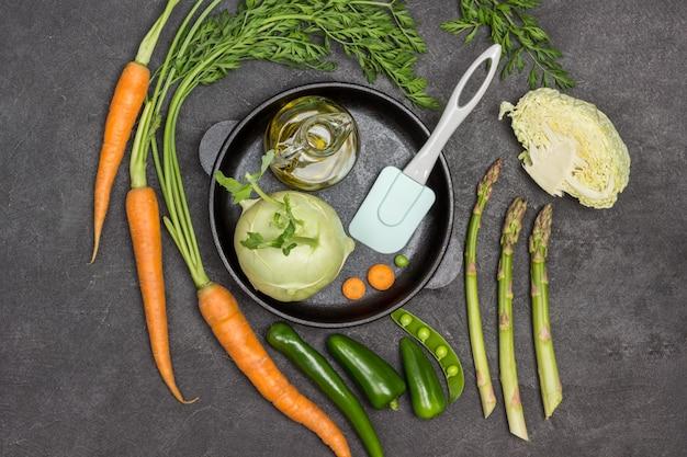 Flasche olivenöl, kohlrabi-kohl in der pfanne. frische karotten mit grünen spitzen, grüne paprikaschote, spargel und grüne erbsen auf dem tisch. schwarzer hintergrund. flach legen