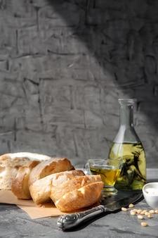Flasche olivenöl mit frischem brot auf dem tisch