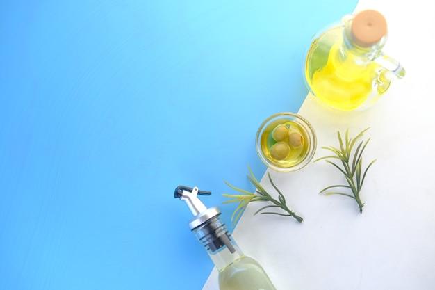 Flasche olivenöl und frische oliven in einem behälter auf farbe